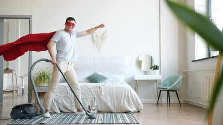 emelt : Portrait of smiling superhero in red cape fluttering in wind and mask vacuuming carpet at home and looking at camera. People, apartment and technology concept.