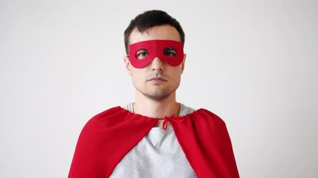 disguise : Portrait of young man in superhero costume red mask and cape looking at camera with serious face standing alone. People, lifestyle and superhero concept.