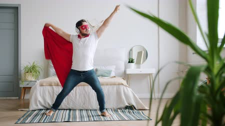 disfarçar : Guy in headphones wearing super hero costume red cape and mask is dancing at home having fun enjoying music and leisure time. People and lifestyle concept.