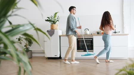 mopping : Husband and wife attractive young couple are dancing in kitchen doing housework together holding mop and duster. People, lifestyle and fun concept.