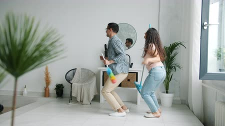 mopping : Funny couple man and woman are danicng in bathroom with duster and mop having fun together enjoying pop music. Youth, relationship and housework concept.