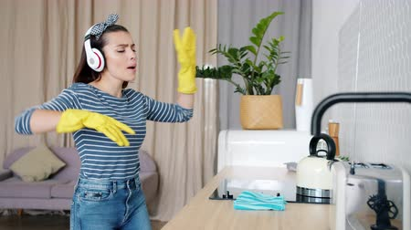 работа по дому : Girl in headphones is singing and dancing then cleaning kitchen wearing rubber gloves using wet cloth caring for hygiene in apartment. Lifestyle and housework concept.