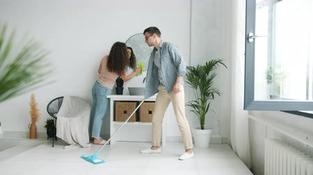 mopping : Slow motion of young family husband and wife washing floor and mirror in bathroom at home doing housework together. Housekeeping and lifestyle concept.