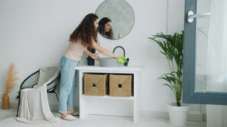 temizleme maddesi : Young beautiful woman is washing washbasin in bathroom doing housework at home alone. Tidy apartment, hygiene and modern youth lifestyle concept. Stok Video