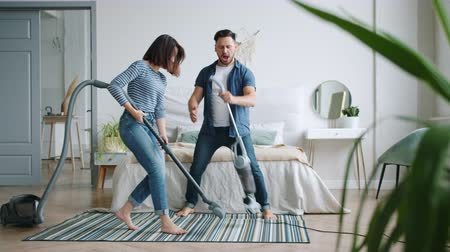 taniec : Man and woman happy couple are having fun at home vacuuming carpet in bedroom dancing singing enjoying music, girl is clapping hands. People and lifestyle concept. Wideo