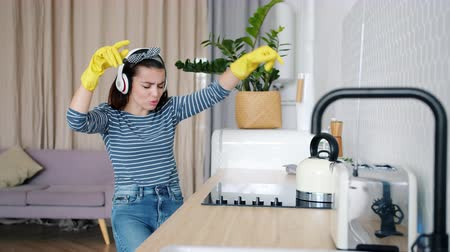 housekeeper : Joyful young lady is cleaning kitchen then dancing and singing enjoying music in wireless headphones. Modern lifestyle, devices and youth concept. Stock Footage