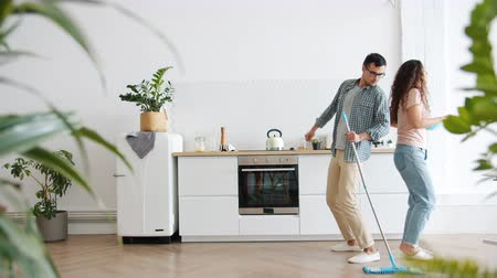 mopping : Girl and guy happy couple are dancing with mop and duster doing housework in kitchen enjoying music and liesure time. People and relaxation concept.