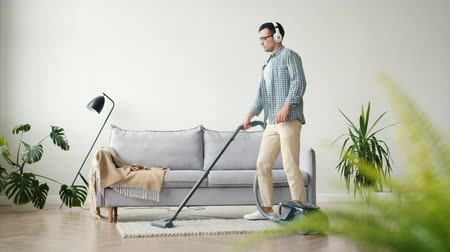 arrumado : Attractive guy is vacuuming flat floor with vacuum cleaner dancing wearing headphones listening to music having fun. Lifestyle and modern devices concept.