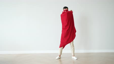 disguise : Slow motion of man in superhero mask costume hiding behind red cape standing against color background. super power and character concept.