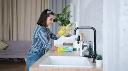 arrumado : Pretty young woman is dusting furniture in kitchen with wet cloth dancing smiling enjoying housework at home. Housekeeping and pretty girls concept. Vídeos
