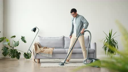 vácuo : Guy in casual clothing is doing housework at home vacuuming carpet in studio apartment concentrated on work. Young people, lifestyle and household concept.