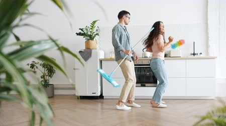 mopping : Slow motion of young family husband and wife dancing in kitchen during clean-up with mop and duster having fun. Lifestyle and joyful youth concept.