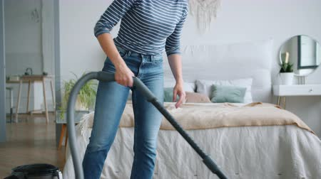 dikkatli : Tilt-down of young lady in casual clothing cleaning carpet with vacuum cleaner in bedroom enjoying housework smiling. People, housekeeping and youth concept.