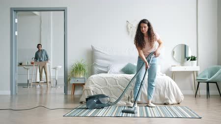 arrumado : Young woman is vacuuming carpet while man husband is dusting furniture in headphones singing having fun during clean-up. Lifestyle and technology concept.