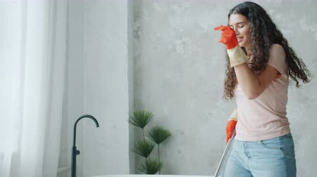 mopping : Tilt-down shot of pretty housewife dancing during clean-up in bathroom mopping floor with plastic mop and having fun. Lifestyle and household concept.
