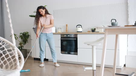 mopping : Female student happy girl is washing floor in kitchen with mop doing housework in apartment busy with sanitary activities. Lifestyle and housekeeping concept. Stock Footage