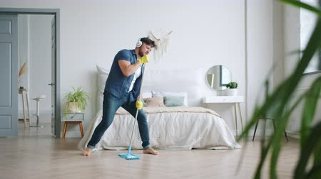 laminát : Joyful guy in wireless headphones is singing in mop washing floor at home having fun listening to rock music. Happy people, housework and gadgets concept.