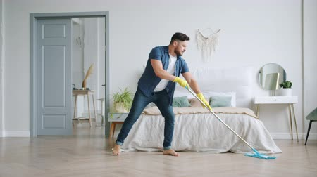 arrumado : Guy in rubber gloves is mopping floor in apartment and dancing with plastic mop having fun doing housework activities. Lifestyle and home occupation concept.