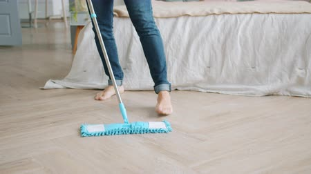 mopping : Handsome bearded guy in casual clothing is cleaning bedroom floor with modern mop doing housework alone. Lifestyle, apartment and people concept.