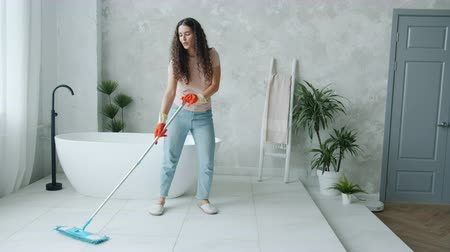 mopping : Happy young lady is washing floor with mop and dancing at home in kitchen enjoying housekeeping activities. People, modern lifestyle and youth concept.