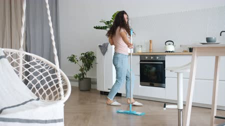 laminát : Joyful young woman is dancing with mop during clean-up in kitchen having fun alone enjoying housework in flat. People, relaxation and chores concept.