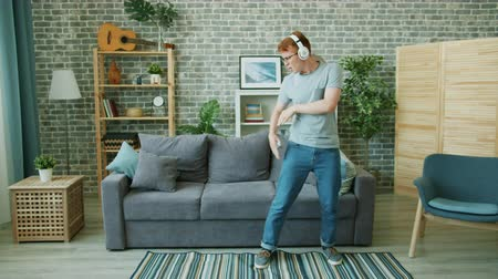 Joyful teenager in headphones is dancing singing in remote control enjoying music in apartment alone. Modern technology, lifestyle and happiness concept.