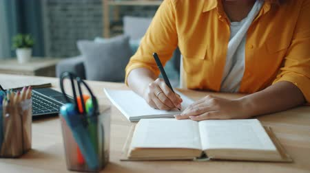 diligence : Close-up of female hand writing in notebook while woman reading book at table at home studying in apartment. People, education and literature concept. Stock Footage