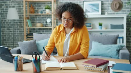 diligence : African American teenager girl is studying at home writing reading book sitting at desk alone. Self education, people and youth culture and lifestyle concept.