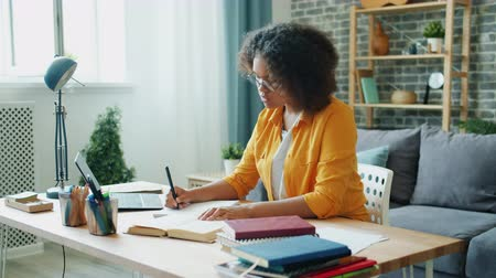 Slow motion of Afro-American student attractive young lady doing homework in apartment writing reading book concentrated on education. People and home concept.