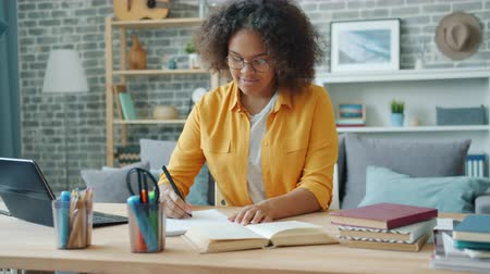 diligence : Smiling young woman in glasses is writing in notebook sitting at desk at home working at project alone. Education, teenage culture and apartment concept.