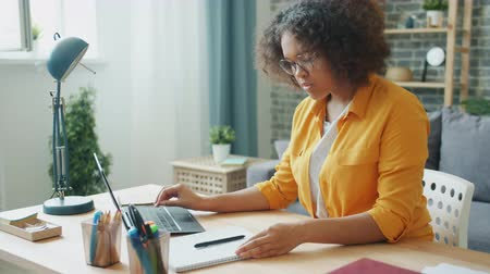 distante : Female student attractive young girl in glasses is studying at home using laptop typing then writing in notebook. Education, people and lifestyle concept. Stock Footage
