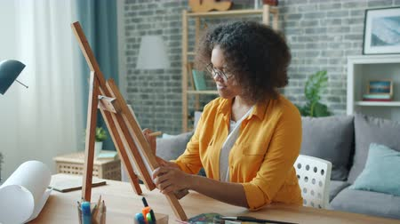 Slow motion of young artist African American girl painting at home at desk using easel, paints and pencil. Apartment, creative youth and occupation concept. Stockvideo