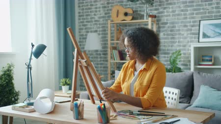 cavalete : Teenage girl is painting picture at home working alone using easel and pencil sitting at desk in apartment. People, creativity and inspiration concept.