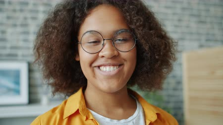 Close-up slow motion portrait of cheerful young woman with curly hair looking at camera and smiling expressing positive emotions. People and fun concept.