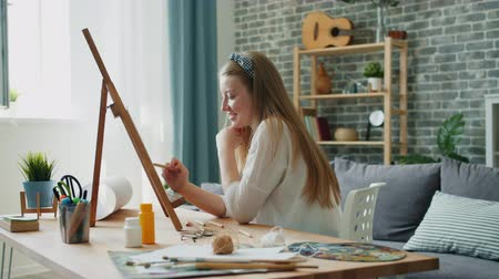 cavalete : Young woman designer is drawing picture at home sitting at easel in apartment using colored pencils. Creative people, occupation and students concept. Vídeos