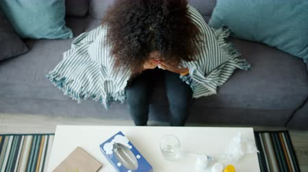 tosse : High angle view of African American teenager sneezing in paper tissue in apartment sitting on couch alone, table with pills is visible. Health problems and people concept.