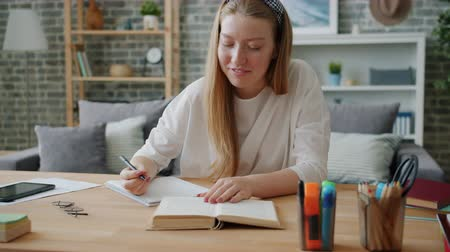 Smiling young lady student is writing in notebook sitting at desk at home working at project alone. Education, teenage culture and apartment concept.