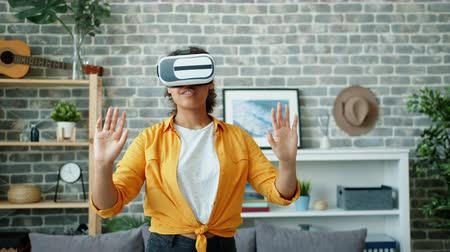Young African American lady is enjoying vr glasses in apartment moving hands having fun indoors alone. Home activities, lifestyle and modern devices concept. Stockvideo