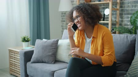 Slow motion of young African American woman laughing talking on mobile phone at home sitting on couch in apartment. People and communication concept.