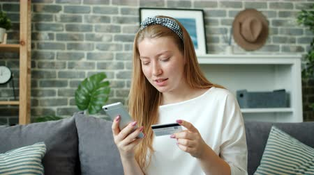 Cheerful young lady is shopping online paying with credit card using smartphone at home laughing enjoying electronic money. Lifestyle and technology concept.