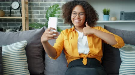 Happy Afro-American teenager is taking selfie with thumbs-up hand gesture at home posing holding smartphone camera. Youth, self-portrait and lifestyle concept. Stockvideo