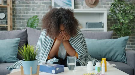 Slow motion of sick African American lady sneezing in paper tissue at home covered with blanket sitting on couch alone feeling bad. People and health concept.