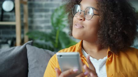 Happy African American teenager is using smartphone at home laughing enjoying social media and modern gadget. Technology, people and lifestyle concept.