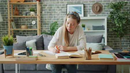 markeerstift : Cute student attractive blond lady is writing in notebook highlighting information and reading book at home sitting at desk. People and education concept.