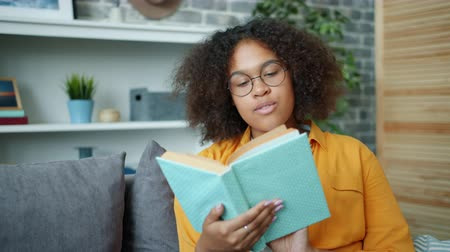 Attractive Afro-American girl in glasses is reading book and smiling sitting on sofa in apartment enjoying literature. Modern people, lifestyle and leisure time concept.