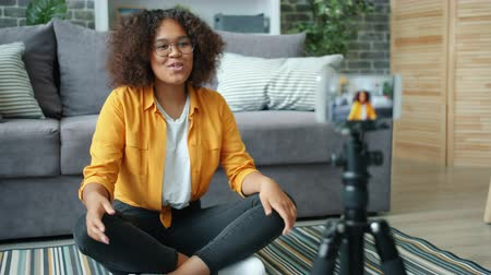 Young African American lady vlogger recording video with smartphone at home showing thumbs-up hand gesture speaking to camera. Youth and blogging concept.