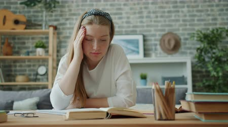 Unhappy child teenage girl is touching head sitting at desk then writing in notebook reading book doing homework. Childhood, lifestyle and fatigue concept.