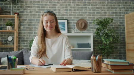 Cheerful girl is finishing homework relaxing smiling sitting at desk in apartment closing book feeling happy. People, education and emotions concept.