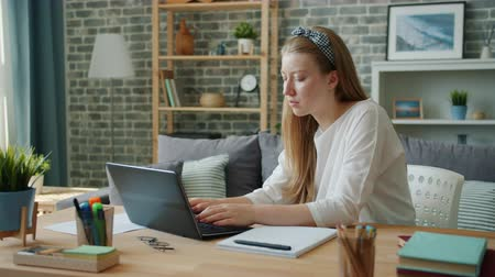 Female student pretty young woman is studying at home using laptop typing then writing in notebook. Education, people and modern lifestyle concept.