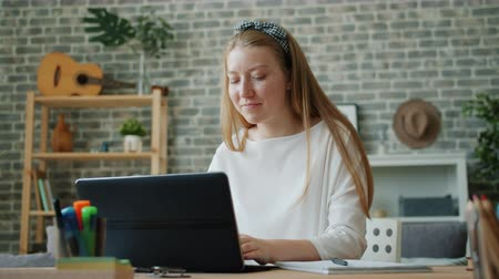 Cheerful teenage girl is using laptop at home smiling then taking notes in notebook writing down information from internet. People and technology concept.